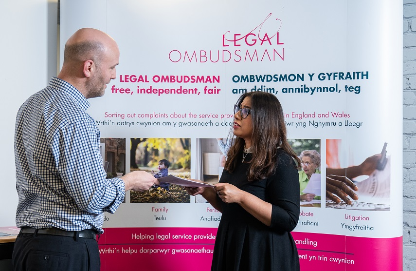man and woman talking by Legal Ombudsman banner