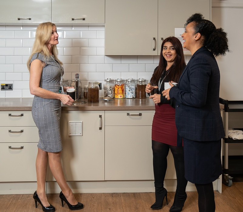 Three female office workers at work tea point